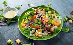 与鸡胸脯、桃子、红洋葱、油煎方型小面包片和菜的新鲜的沙拉在一块绿色板材 健康的食物 免版税库存图片