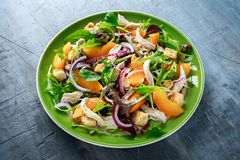 与鸡胸脯、桃子、红洋葱、油煎方型小面包片和菜的新鲜的沙拉在一块绿色板材 健康的食物 库存图片