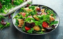 与鸡胸脯、芝麻菜、坚果和蕃茄的新鲜的沙拉在黑色的盘子在一张木桌里 库存照片