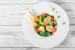 与鸡胸脯,婴孩菠菜,蓬蒿,西红柿,梨,在板材的黄瓜的新鲜的沙拉在木背景关闭 免版税图库摄影