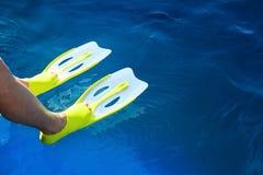 与鸭脚板的脚在蓝色海,当潜航时 免版税库存图片