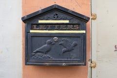 与鸽子浅浮雕,有油漆白色条纹的桃红色墙壁的黑葡萄酒金属邮箱在边的 免版税库存照片