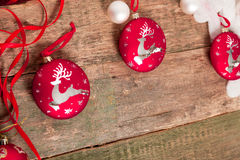 与鹿和丝带的红色圣诞节球在木背景 invitation new year 框架 复制空间 图库摄影