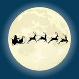 与鹿的圣诞老人剪影在月亮前面 免版税库存照片