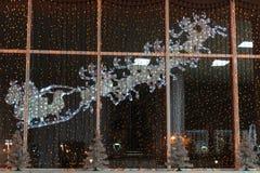与鹿装饰光的圣诞老人的雪橇在窗口 免版税库存照片