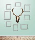 与鹿角吊的银色框架装饰在与轻flar的墙纸 库存照片
