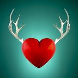 与鹿角的红色心脏在绿松石背景 免版税图库摄影