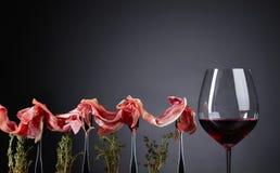 与麝香草枝杈和杯的熏火腿在黑暗后面的红葡萄酒 免版税图库摄影