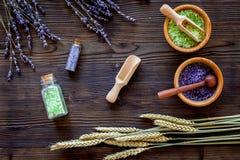 与麦子和淡紫色草本化妆盐的家庭温泉在木书桌背景顶视图的浴的 免版税库存照片