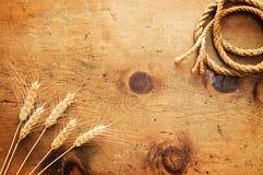 与麦子和绳索的小尖峰的葡萄酒木桌 免版税库存照片