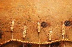 与麦子和绳索的小尖峰的葡萄酒木桌 库存图片