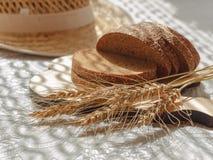 与麦子小尖峰的切的面包在木砧板和被弄脏的草帽在背景 图库摄影
