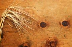 与麦子的小尖峰的葡萄酒木桌 免版税库存照片
