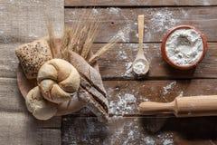 与麦子耳朵和面粉的面包在木板,顶视图 免版税图库摄影