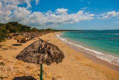 与黄沙,蓝色加勒比海、可可椰子和伞的热带风景 西恩富戈斯,古巴,兰乔月/月球海滩 库存照片