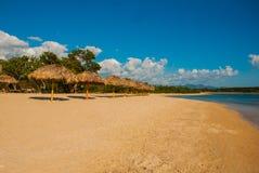 与黄沙,蓝色加勒比海、可可椰子和伞的热带风景 西恩富戈斯,古巴,兰乔月/月球海滩 免版税库存照片