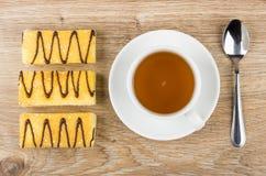 与黄油奶油,茶的三个蛋糕在茶碟的 免版税库存照片