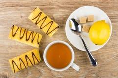 与黄油奶油,茶,茶碟的蛋糕用柠檬,糖 图库摄影
