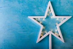 与黄灯的白色圣诞节星在蓝色背景 免版税库存照片