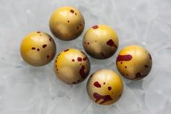 与黄色光亮的涂层的手工制造巧克力糖与以一个半球的形式RED丢弃在一白色表面无光泽的玻璃backgroun 免版税图库摄影