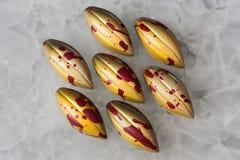 与黄色光亮的涂层的手工制造巧克力糖与以一把柳叶刀的形式RED丢弃在白色表面无光泽的玻璃背景 免版税库存图片