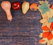 与黄色叶子、红色苹果和南瓜的秋天背景 免版税库存图片