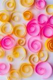 与黄色和桃红色纸螺旋和漩涡,纸艺术的背景;招呼/周年卡片概念 库存图片