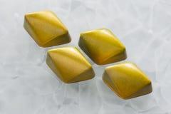 与黄色和绿色光亮的涂层的手工制造巧克力糖以在白色表面无光泽的玻璃背景的菱形的形式 库存图片