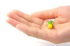 与黄色和绿色的一个胶囊在一个美好的妇女现有量 库存照片