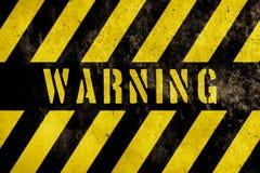 与黄色和黑暗的条纹的警报信号文本被绘在混凝土墙门面纹理背景 免版税图库摄影
