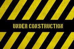 与黄色和黑条纹的建设中警告危险标志被绘在混凝土墙粗糙的门面纹理背景 库存图片