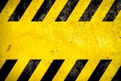 与黄色和黑条纹的警告背景被绘在黄色混凝土墙门面纹理和空的空间正文消息的 库存图片