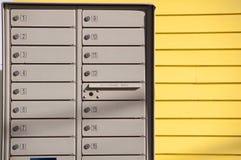 与黄色房屋板壁的邮箱行和墙壁 库存图片