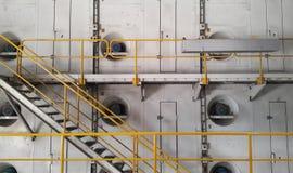 与黄色扶手栏杆的步行方式在造纸机的边 免版税库存图片