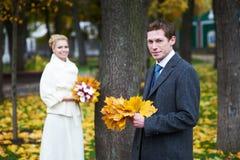 与黄色枫叶的新娘和新郎 免版税库存照片
