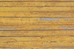 与黄色油漆的遗骸的葡萄酒木板条作为背景的 图库摄影