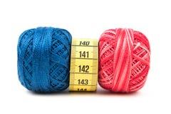与黄色测量的磁带的蓝色和红色缝合针线在白色背景 库存照片