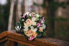 与黄色玫瑰、白色菊花和桃红色德国锥脚形酒杯的美丽的婚礼花束 免版税库存照片