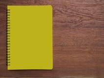 与黄色笔记本和文具的木头 免版税图库摄影