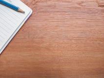与黄色笔记本和文具的木头 免版税库存照片