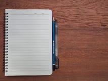 与黄色笔记本和文具的木头 库存图片