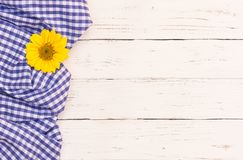 与黄色花开花的蓝色野餐桌布在土气白色木桌背景 免版税库存图片