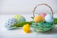 与黄色郁金香的五颜六色的复活节彩蛋手画在白色木背景 欢乐春天卡片 免版税库存照片