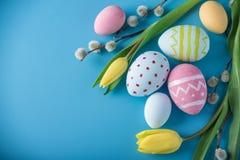 与黄色郁金香的五颜六色的复活节彩蛋手画在蓝色背景 假日春天卡片 免版税库存图片