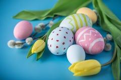 与黄色郁金香的五颜六色的复活节彩蛋手画在蓝色背景 假日春天卡片 免版税图库摄影