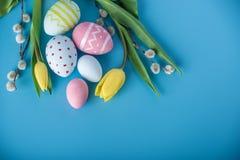 与黄色郁金香的五颜六色的复活节彩蛋手画在蓝色背景 假日春天卡片 图库摄影