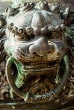 与黄铜的古色古香的中国狮子铸件 图库摄影