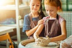 与黏土横式转盘的运作的过程 做瓦器的两个女孩在演播室 免版税库存照片