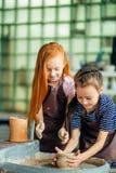 与黏土横式转盘的运作的过程 做瓦器的两个女孩在演播室 库存照片