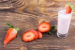 与黏浆状物质的草莓酸奶在一个木板 图库摄影